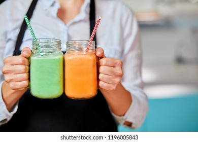 woman is holding two glasses of detox coktails. close up cropped photo. drink for lossing weight