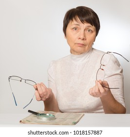 Woman holding two glasses in her hands. Bad vision, unsuitable glasses