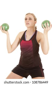 A woman is holding two medicine balls and working out.