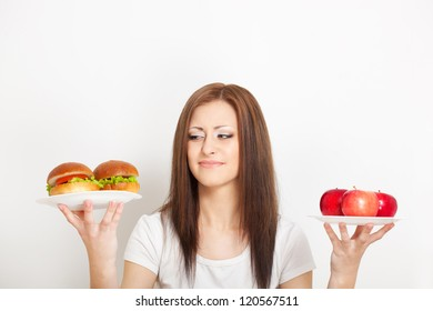 woman holding two plates with junk food and apples and looking to the hamburgers