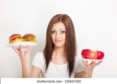 woman holding two plates with junk food and apples