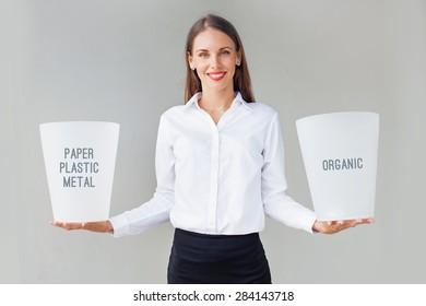 woman holding two rubbish bins for garbage segregation