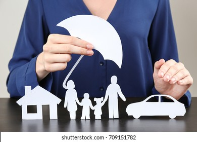 Woman holding umbrella over paper silhouette of family, house and car on table. Insurance concept