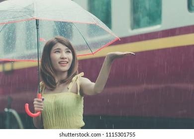 Woman holding umbrella in rainy day. Asian girl on spring season at train station. Lady happy rainy season concept.
