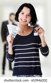 Woman holding US dollars bills and house model