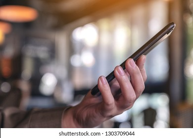 A woman holding and using a black smart phone with blur background in cafe
