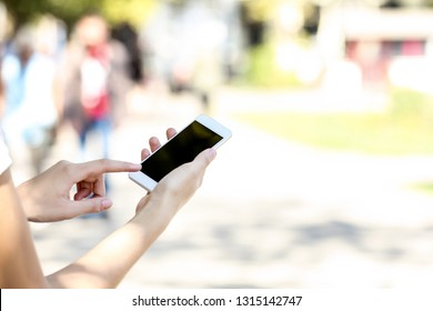 Woman holding and using smartphone on blurred background