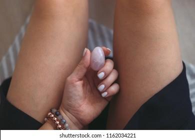Woman holding vaginal (yoni) egg betweet her legs. Rose quartz crystal egg
