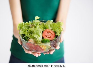 woman holding vegetable salad bowl close up over white background with out of focus blur style on body