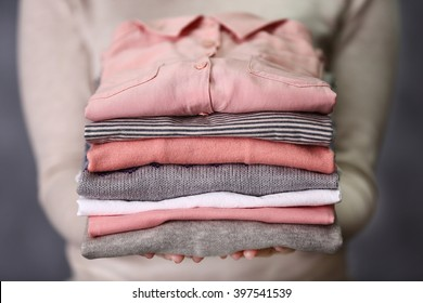 Woman holding washed and dried clothes on grey background