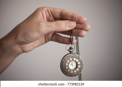 a woman is holding a watch on a chain on a gray background. The time on the clock 11:55 PM