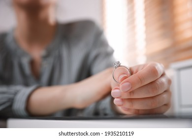 Woman holding wedding ring at table indoors, space for text. Divorce concept