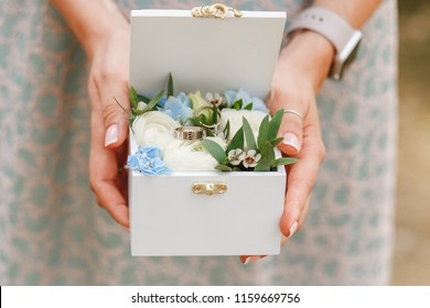 Woman holding wedding rings in wooden box decorated with flowers. Close horizontal photo.