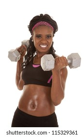 A woman  holding weights with a smile on her face working out her arms.