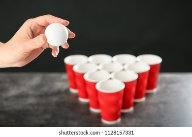 Woman holding white ball near plastic cups arranged for playing beer pong, closeup