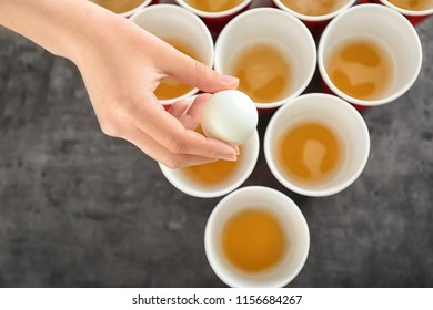 Woman holding white ball over cups arranged for playing beer pong, closeup