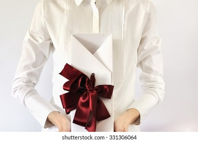 Woman holding a white box tied  with the ribbon