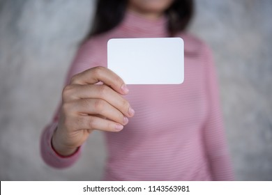 Woman holding white business card on concrete wall background