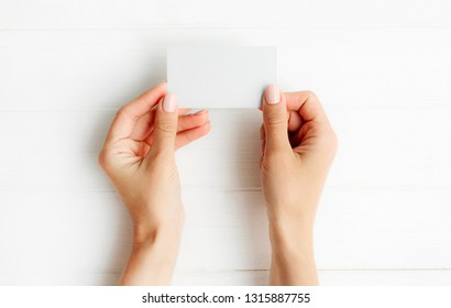 Woman holding white business card in hands. Tamplate for your design.