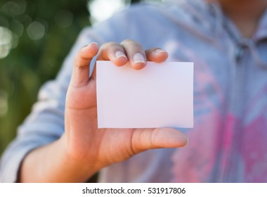 Woman holding white business card.