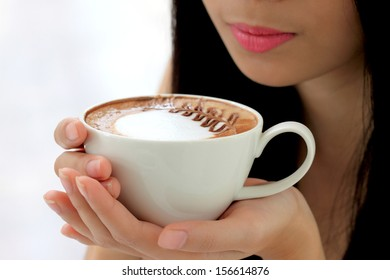 woman holding white coffee cup