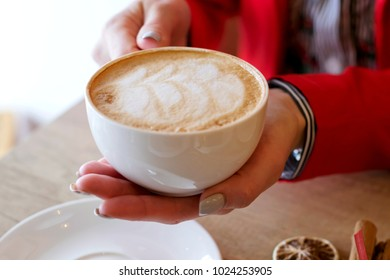 Woman holding white cup with morning cappuccino. Mug in hand.