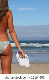 woman holding white flops on the shoreline