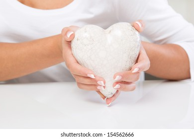 Woman holding a white heart - medical assistant