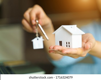 Woman holding white house model and house key in hand.Mortgage loan approval  home loan and insurance concept.