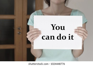 Woman holding white paper with text You can do it