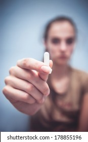 Woman holding white pill in her hand