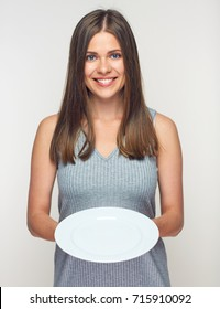 Woman holding white plate. Smiling girl waitress isolated.
