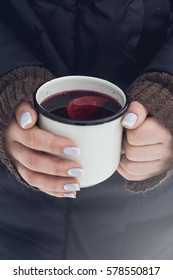 Woman holding white rustic mug of mulled wine with spices and citrus fruit  in her hands outdoors in cold winter day, close up