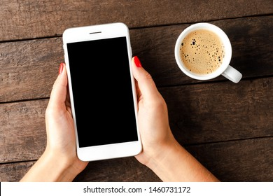 Woman holding white smart phone with copyspace.