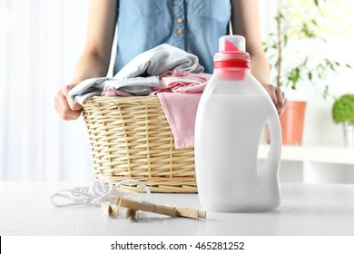 Woman holding wicker basket with clothes and detergent on table