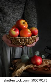 woman holding a wicker basket with ripe apples in their hands