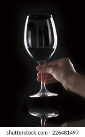 A woman holding wine glass on the reflective bottom isolated black.