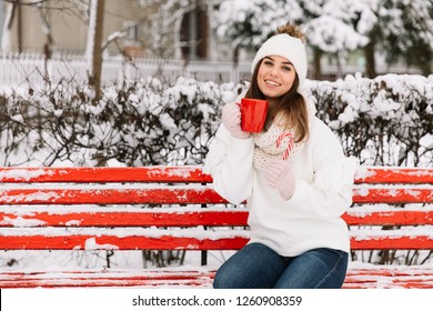 Woman holding winter cup close up on park. Woman hands in gloves holding a cozy mug with hot cocoa, tea or coffee and a candy cane. Winter and Christmas time concept.