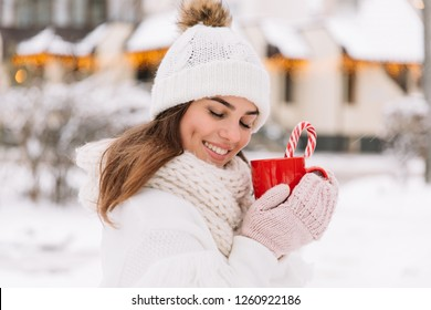 Woman holding winter cup close up on street or park. Woman hands in gloves holding a cozy mug with hot cocoa, tea or coffee and a candy cane. Winter and Christmas time concept.