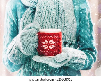 Woman holding winter cup close up on light background. Woman hands in teal gloves holding a cozy mug with hot cocoa, tea or coffee and a candy cane. Winter and Christmas time concept