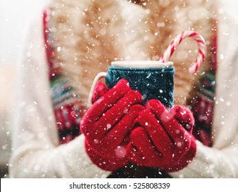 Woman holding winter cup close up on light background. Woman hands in red gloves holding a cozy mug with hot cocoa, tea or coffee and a candy cane. Winter and Christmas time concept