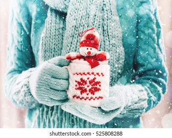 Woman holding winter cup with nice Christmas toy close up on light background with snowfall. Hands in woolen teal gloves holding a cozy mug with happy snowman toy. Winter and Christmas time concept