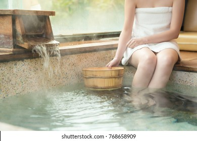 woman holding the wood barrel scoop and sitting on poolside