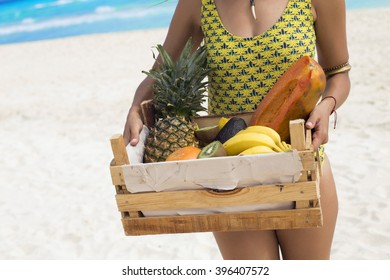 Woman holding a wooden box full of fresh fruit