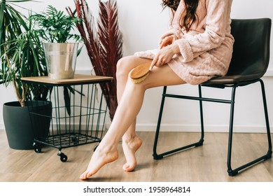Woman holding wooden brush and doing dry massage on her feet. Self care concept