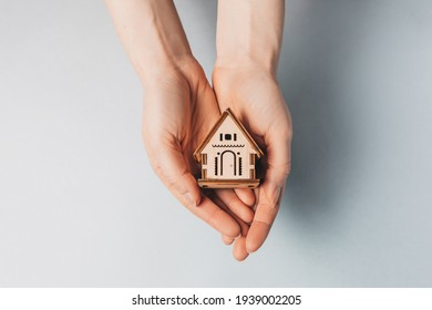 Woman holding a wooden house with her hands with the sun on a light blue background. Sweet home