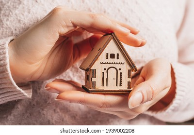 Woman holding a wooden house with her hands with the sun on a light pink background. Sweet home