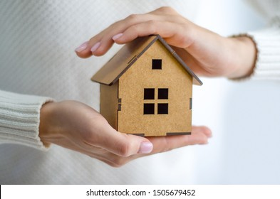 Woman holding wooden model house in hands on white background