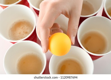 Woman holding yellow ball over cups arranged for playing beer pong, closeup