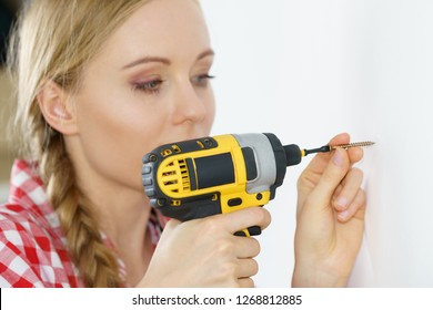 Woman holding yellow driller about to drill something. Hardware construction site objects concept.